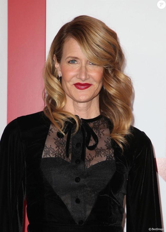 Frisuren halblang für ältere Frauen, goldblonde wellige Haare mit seitlichem Pony, schwarzes Kleid mit langen Ärmeln, roter Lippenstift