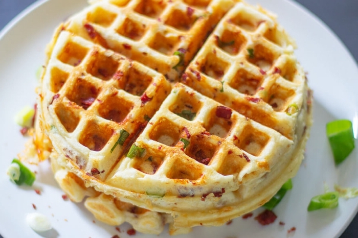 frühstück essen, salzige waffeln mit käse und frühlingszwiebel, weißer teller