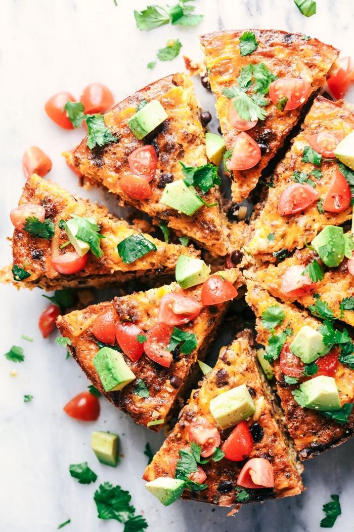 frückstück rezepte, gericht mit eiern, chorizo und kartoffelpuffern garniert mit avocado und tomaten
