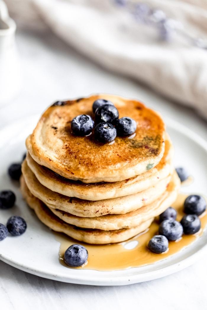 frühstück rezepte, pfannkuchen mit honig und blaubeeren, weißer teller, einfach