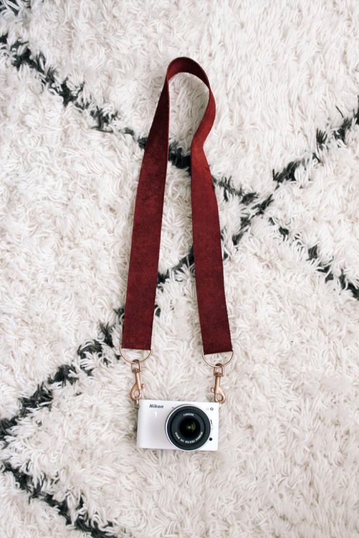 diy geschenke, geburtstagsgeschenk für fraund, weißes fotosapparat, kameratrageriemen aus braunem leder