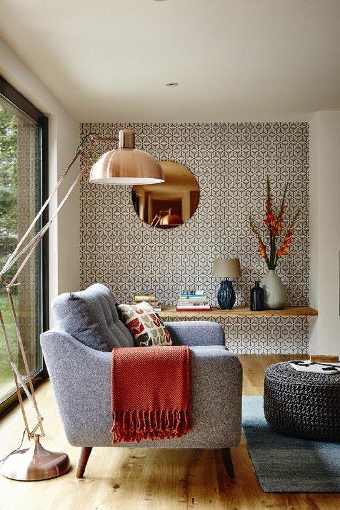 eine Tapete mit geometrischem Muster, ein grauer Sessel, Laminatboden, eine Stehlampe