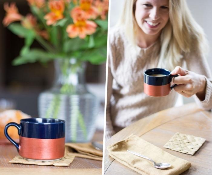kaffee tringen, tisch aus holz, beige bluse, geschirr bemalen, schwarze tasse dekoriert mit kupferfarbiger farbe