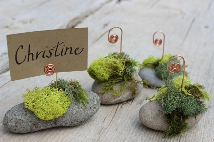 graue Steine, Moos, eine Tabelle mit dem Namen, auf einem Tisch aus Holz, rustikale Ideen für 60. Geburtstag