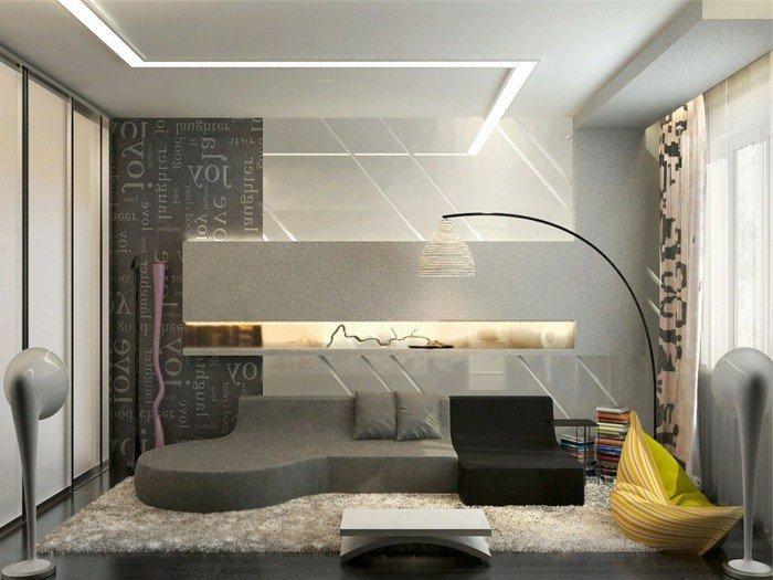 ein graues Sofa, schwarzer Sessel, graue Wandfarbe, eine schwarze Wand, grünes Kissen, Wohnzimmer Ideen für kleine Räume