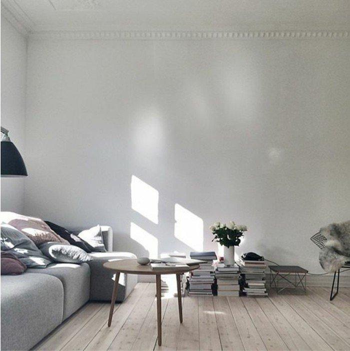 ein runder brauner Tisch, graues Sofa, eine Vase über einen Haufen Bücher, Laminat Boden, Wohnzimmer Ideen für kleine Räume