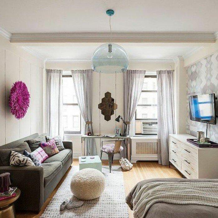 ein graues Sofa, bunte Kissen, ein runde lila Bild, ein weißer Teppich, lila Vorhänge, weißer Hocker, Wohnzimmer Ideen für kleine Räume