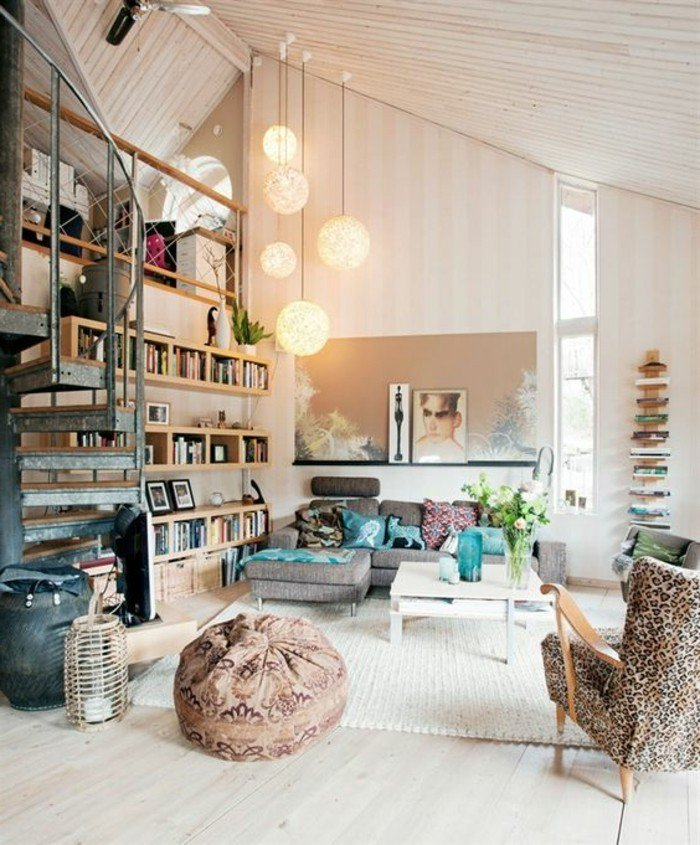 ein graues Sofa, ein weißer Teppich, Regal mit vielen Büchern, brauner Hocker, Wohnzimmer Ideen für kleine Räume