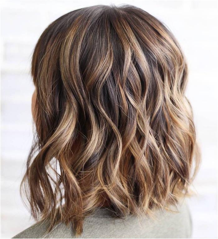 eine frau mit langen braunen strähnchen, braune haare frisuren, junge frau mit einem grauen t-shirt