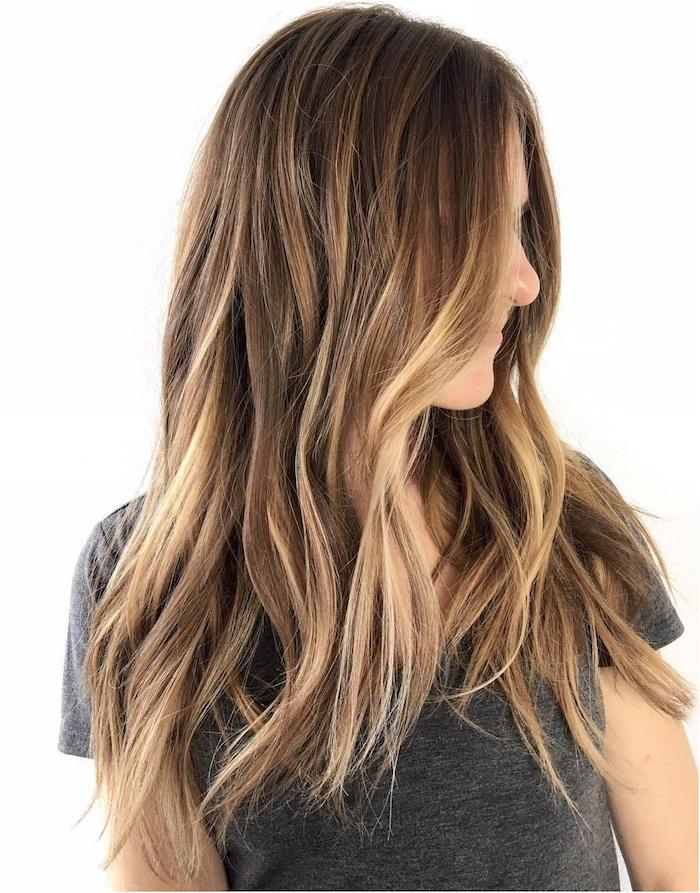 junge frau mit einem grauen t-shirt, eine frau mit einer braunen haare mit langen braunen strähnchen