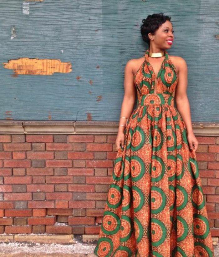 afrikanische mode zum inspirieren, eine lächelnde frau an blauem und robusten hintergrund, orange und grün kleidmuster