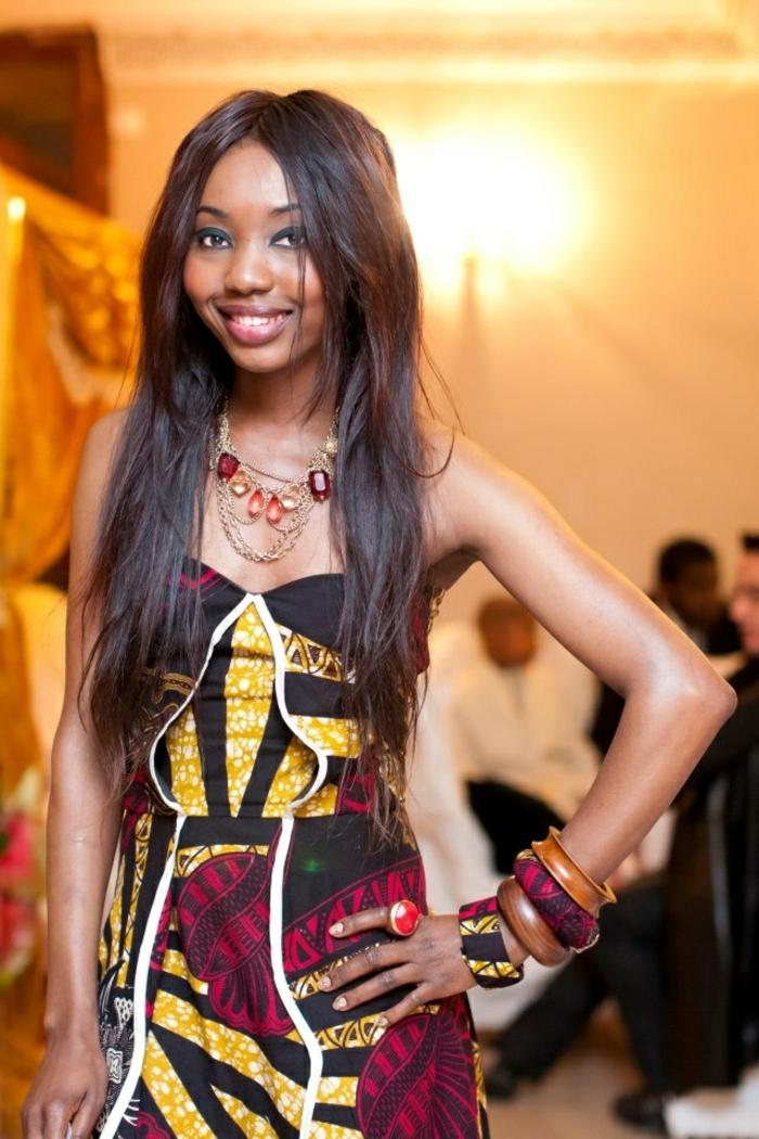 afrikanische mode ideen, eine model mit buntem kleid, farben der erde, gelb, rot, schwarz, weiß, viele armbänder