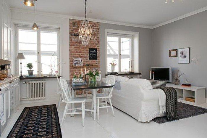 einraumwohnung, robuster look mit modernem interieur kombinieren, weißes sofa mit fernsehwand dagegen, küchenzeile, schwarzer teppich