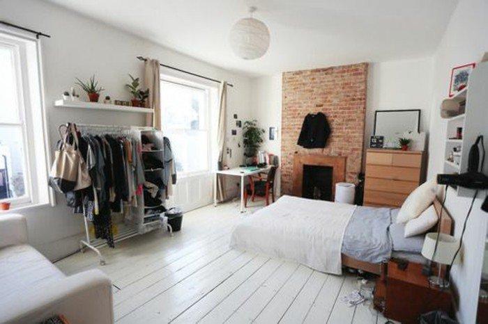 einraumwohnung ideen zum entlehnen, weißer holzboden, doppelbett direkt am boden, kleiderhaken, ziegelwand