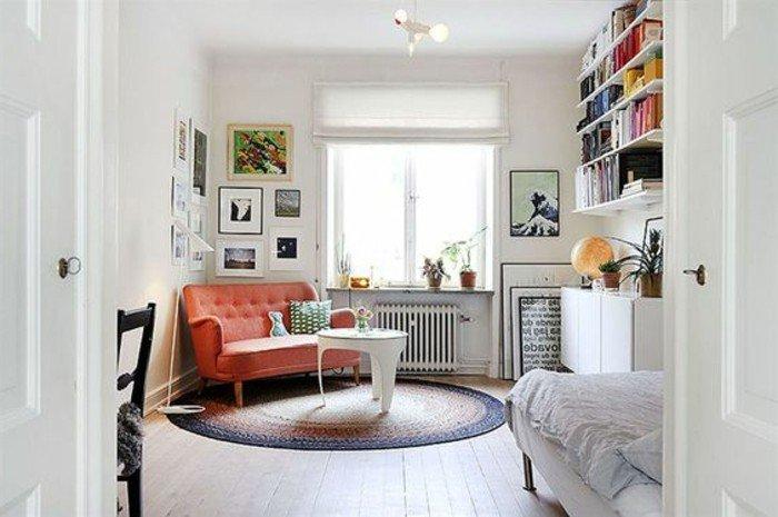 wohnung einrichten, oranges sofa für zwei in der ecke der wohnung gestellt, bett, wandbilder, bücherregale oben rechts