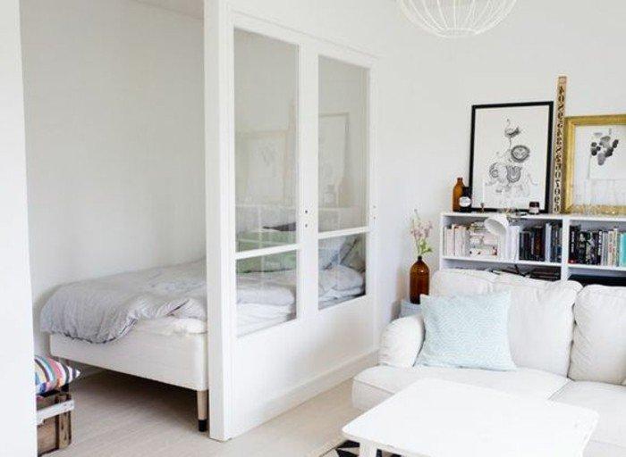 wohnung einrichten, simpler stil, doppelbett mit raumteiler vom wohnbereich getrennt, wandbilder, kissen, deko