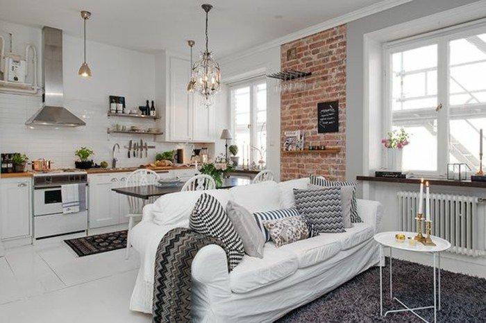 wohnung einrichten, mischung von verschiedenen stilen und designs, ziegelwand, sofa mit vielen kissen, küchenzeile