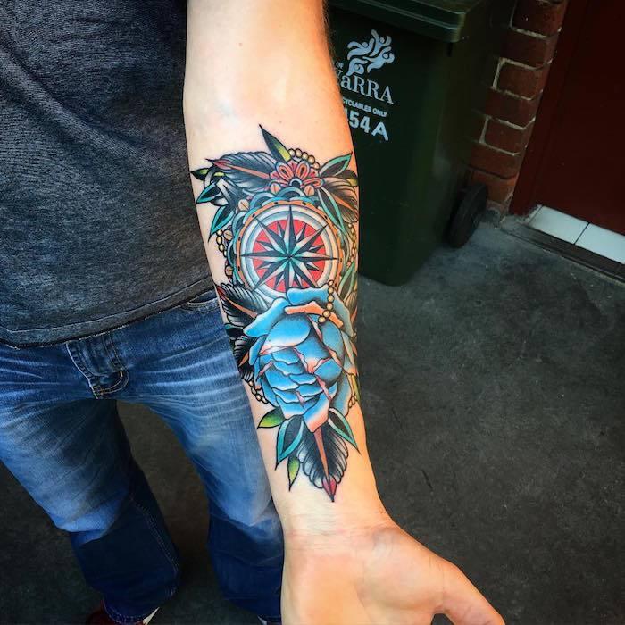 kompass tattoo am unterarm, farbige tätowierung mit floralen motiven, blaue rose