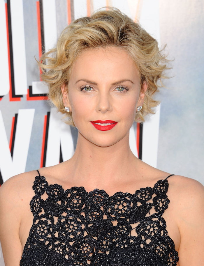 Kurzhaarfrisuren für Frauen ab 40, blonde wellige Haare, schwarzes Spitzenkleid, roter Lippenstift und schwarze Mascara