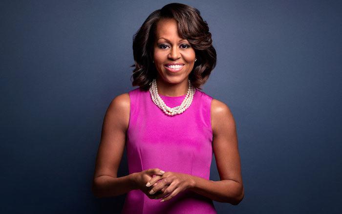 Michelle Obama Hairstyle, halblange schwarze Haare, Kleid in Violett und Perlenkette