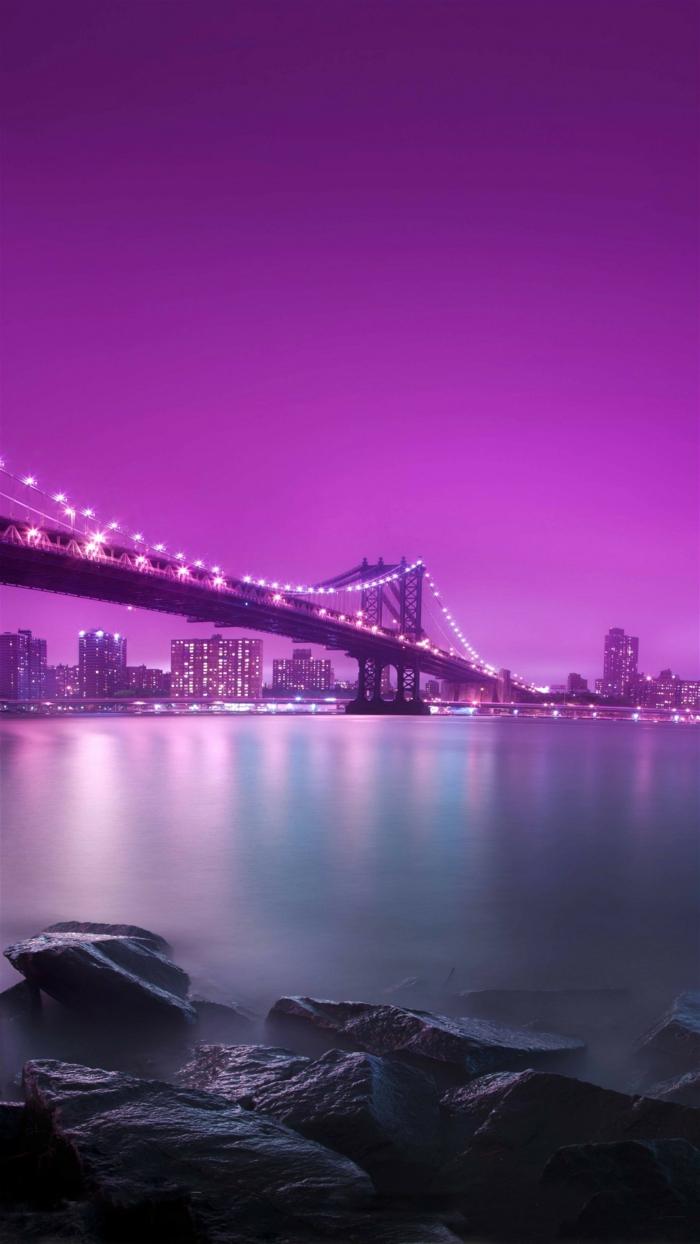 ein lila Himmel, leuchtendes Wasser, Felsen, eine Brücke und ein Großstadt in der Ferne, Hintergrundbilder kostenlos