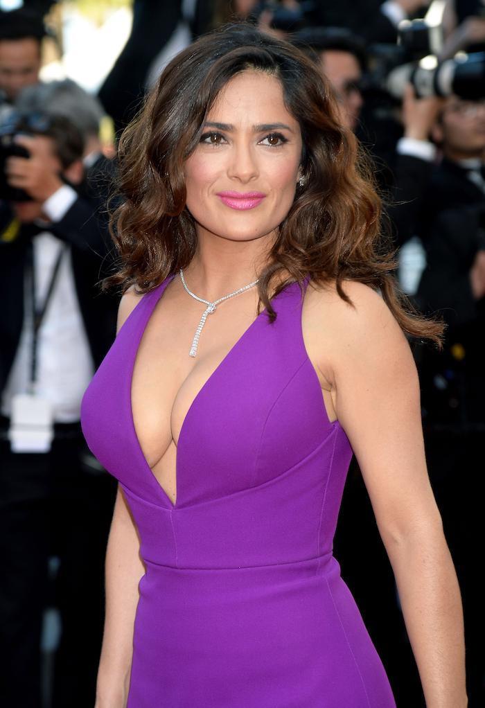 Salma Hayek Haarstyle, mittellange wellige Haare, violettes Abendkleid mit V-Ausschnitt, rosa Lippenstift