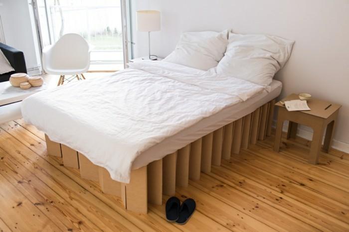 bett design idee, pappmöbel für erwachsene, ein doppelbett mit sessel daneben und pappiertischchen