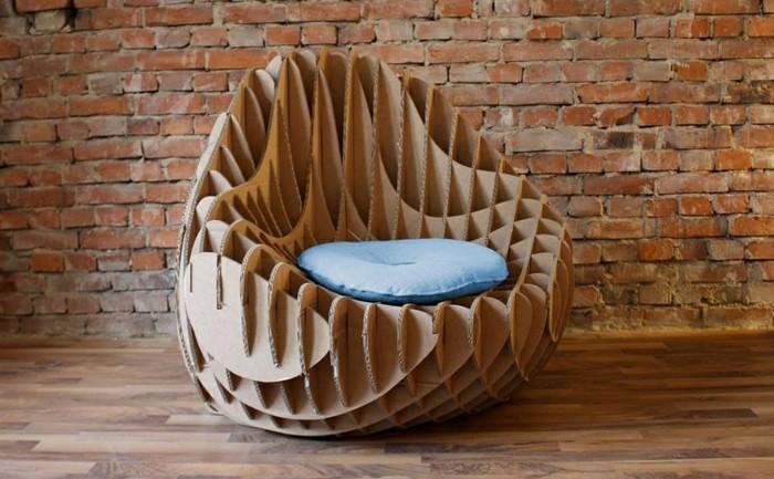 pappmöbel mit kreativer und moderner optik, sessel groß und trendy mit einem blauen kissen darauf