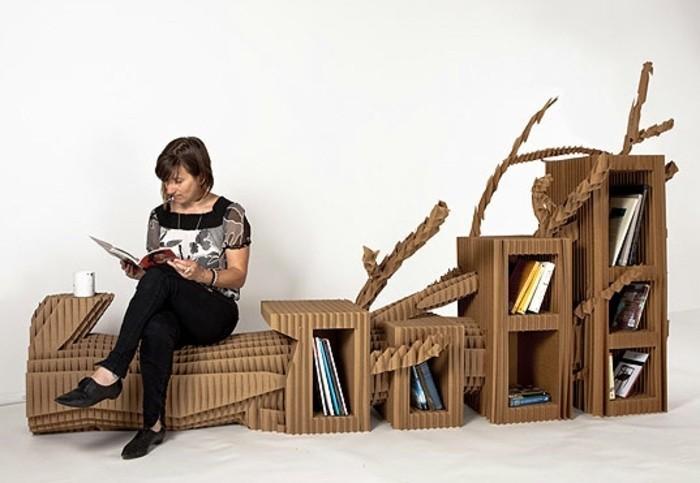 bett pappe, regale, sitzplatz, sitzbönke, eine frau sitzt auf pappsofa mit bücherregalen und liest ihr buch