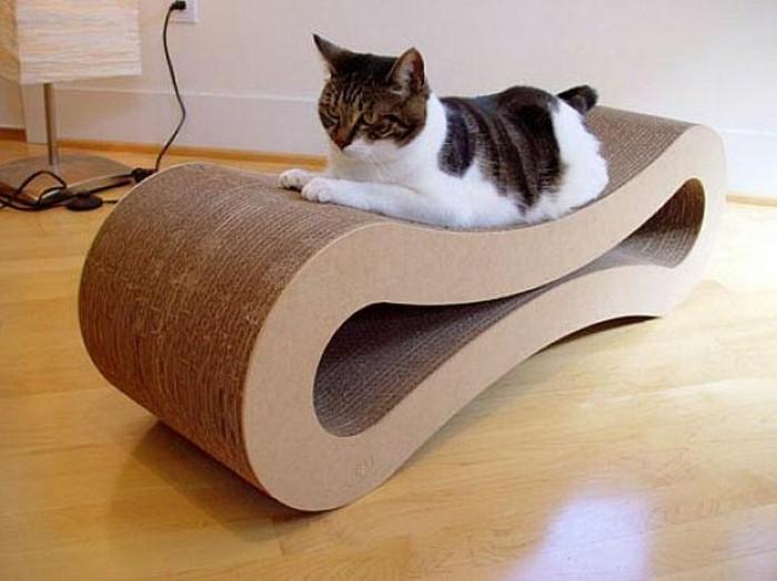 bett pappe, ein sessel aus karton in schöne optik, wellenförmig gemacht, eine katze schläft auf dem sessel