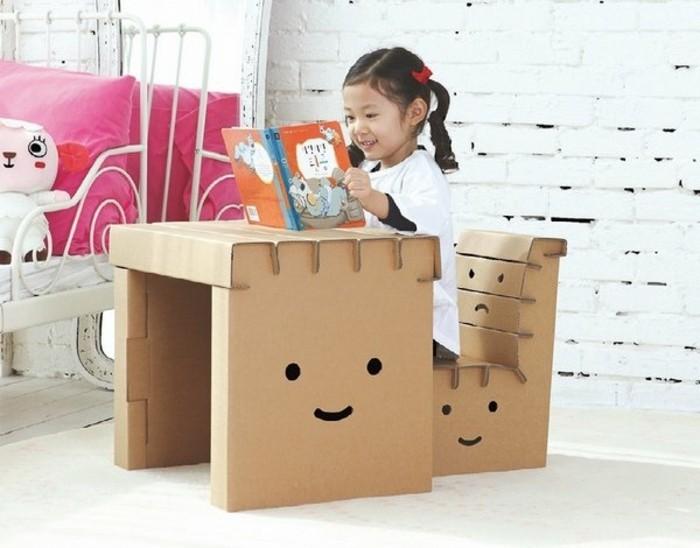 möbel aus karton für das kinderzimmer. ein kleines mädchen sitzt am schreibtisch aus karton und auf einem lustigen kartonstuhl, auf möbel zeichnen, emoji, gesicht zeichnen, kinderbuch lesen