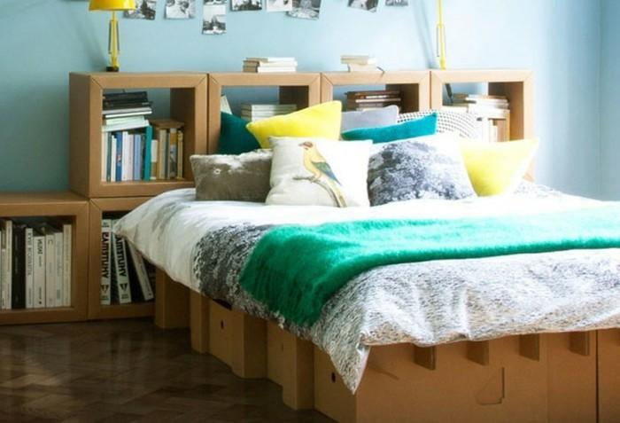 möbel aus karton, pappbett selbst gemacht aus karton und pappregale dahinten, bücherregale, bunte bettwäsche