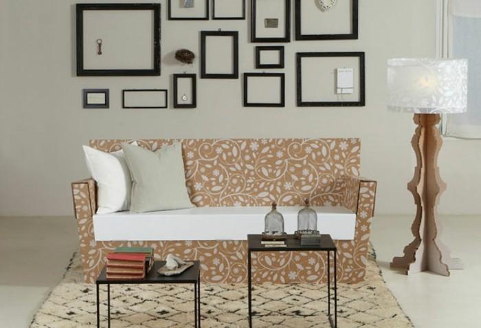 pappmöbel selber machen so funktioniert es, sofa mit schönem dessin aus pappierstoff gemacht, zwei kissen darauf, eine stehlampe, viele bilderrahmen ohne bilder darin, zwei kaffeetischchen