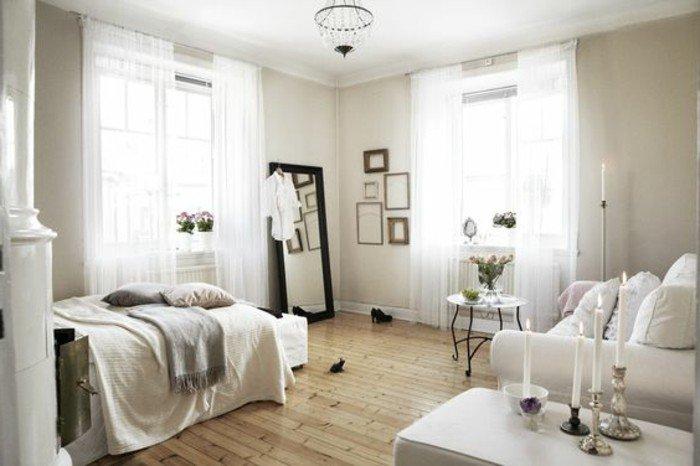 kleines wohnzimmer einrichten ideen zum stilvollen design, großer spiegel, doppelbett, tisch mit vielen kerzen