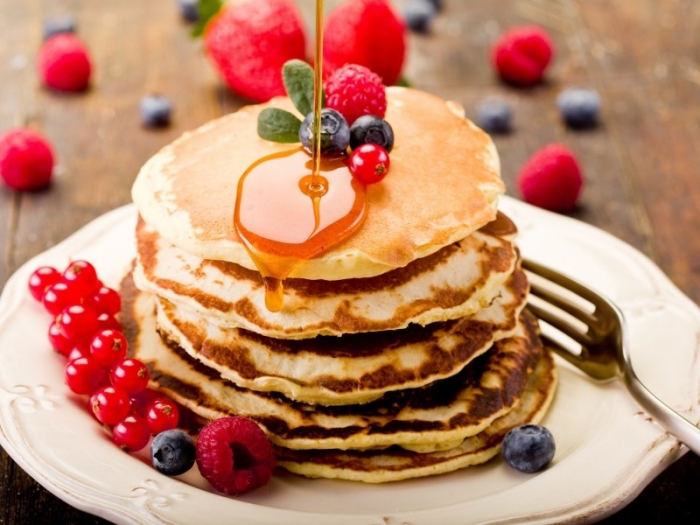 pfannkuchen garniert mit roten beeren, himbeeren und blaubeeren, rezepte frühstück, honig