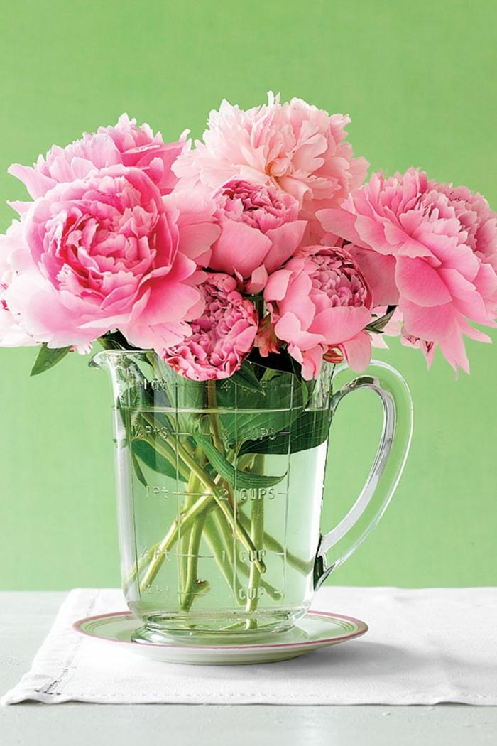 Blumen Tischdeko im Glas, rosa Rosen, eine Kanne voller Wasser, grüner Hintergrund, weißes Tuch