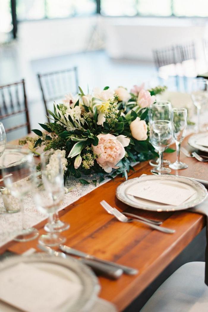 Blumen Tischdeko im Glas, rosa Blumen, goldfarbene Tischläufer, Tisch aus Holz, beige Teller