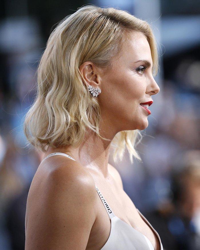 Charlize Theron Haarschnitt, blonde halblange Haare, roter Lippenstift, silberne Ohrringe mit Kristallen, weißes Abendkleid