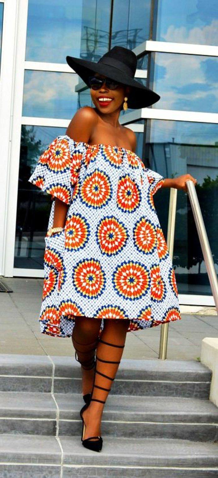 afrikanische stoffe zum inspirieren, buntes kleid mit hellblauer basis und blumenartiger deko in rot, frau mit großem hut, sommerkleidung