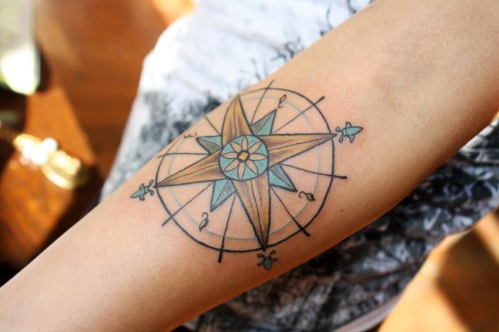 kleine blüte, tätowierung mit kompass als motiv, tattoo vorlagen arm