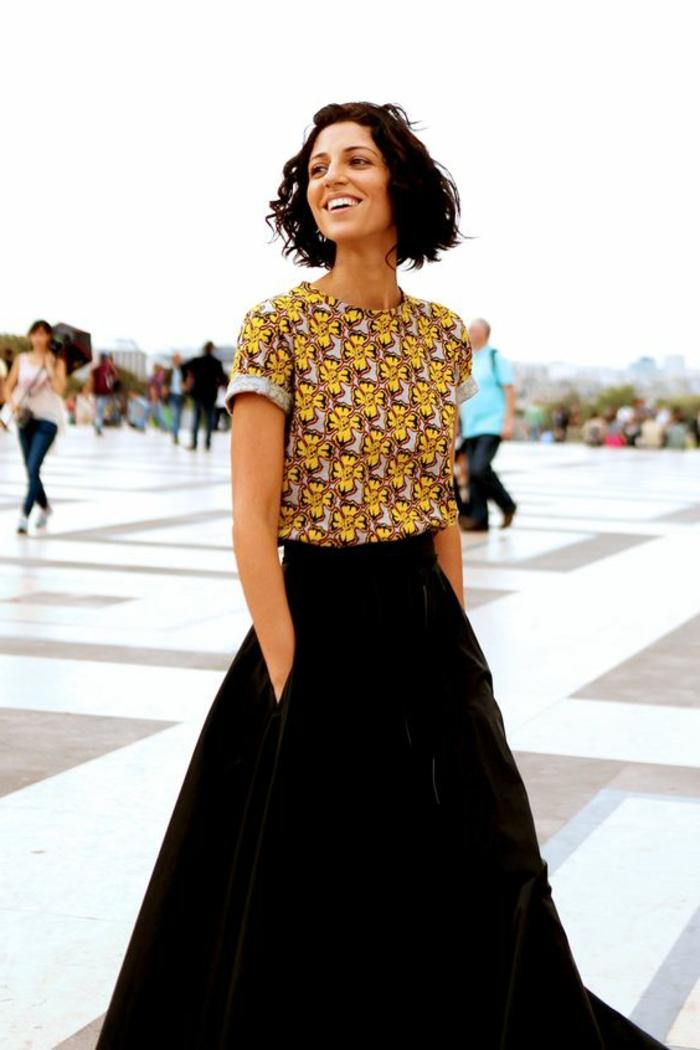 afrikanische kleidung in moderner optik, eine frau geht in paris spazieren mit langem schwarzen rock und kurzes buntes tshirt im afrostyle, kurze kaare, bobschnitt, lächelnde frau