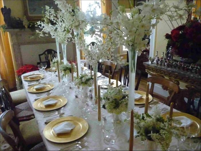 Blumen Tischdeko im Glas, viele hohe Vasen mit weißen Blumen, goldfarbene Teller, weiße Tischdecke
