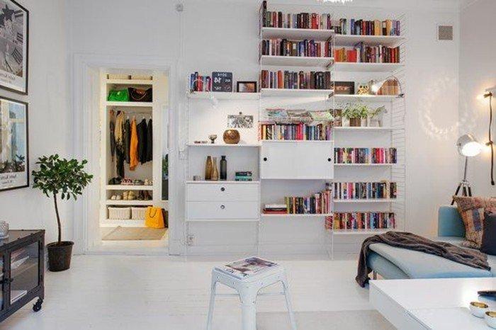weißer Fliesenboden. weißes Regal mit bunten Büchern, eine Garderobe, Wohnzimmer Ideen für kleine Räume