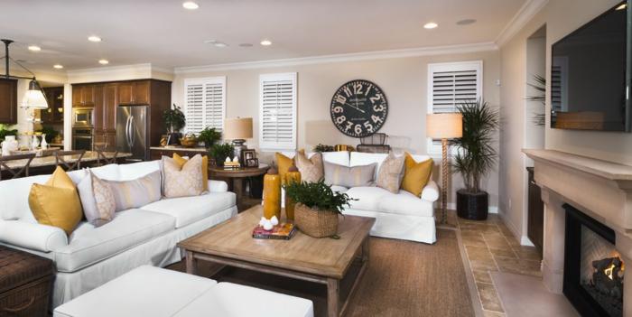 weiße Couches, weiße Hocker, Tisch aus Holz, eine Wanduhr in schwarzer Farbe, ein Kamin, Wandgestaltung Ideen selber machen