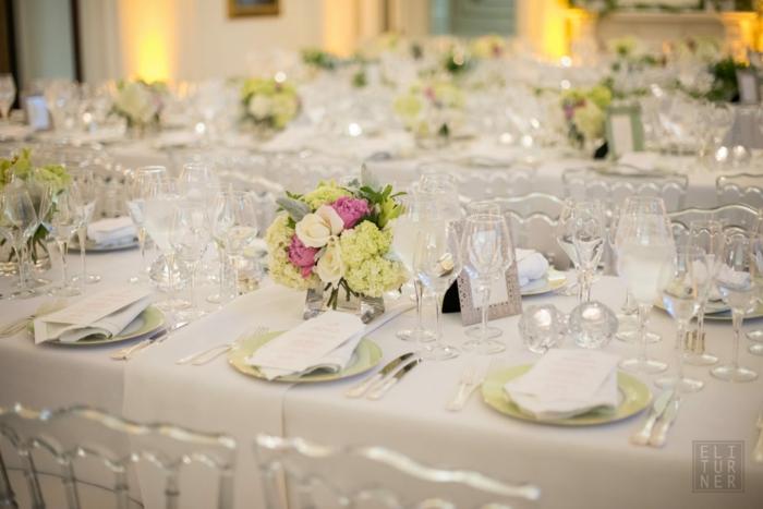 Blumen Tischdeko aus Glas, rosa und grüne Blumen, eine weiße Decke, viele Gläser, Karten mit dem Platz
