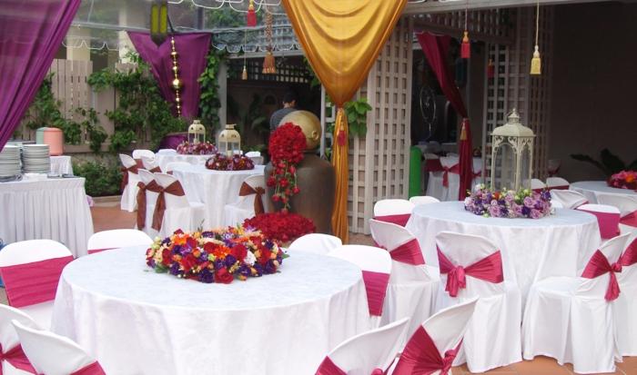 eine weiße Tischdecke, Blumen in der Mitte des Tisches, Schleifen zu der Lehne der Stühle