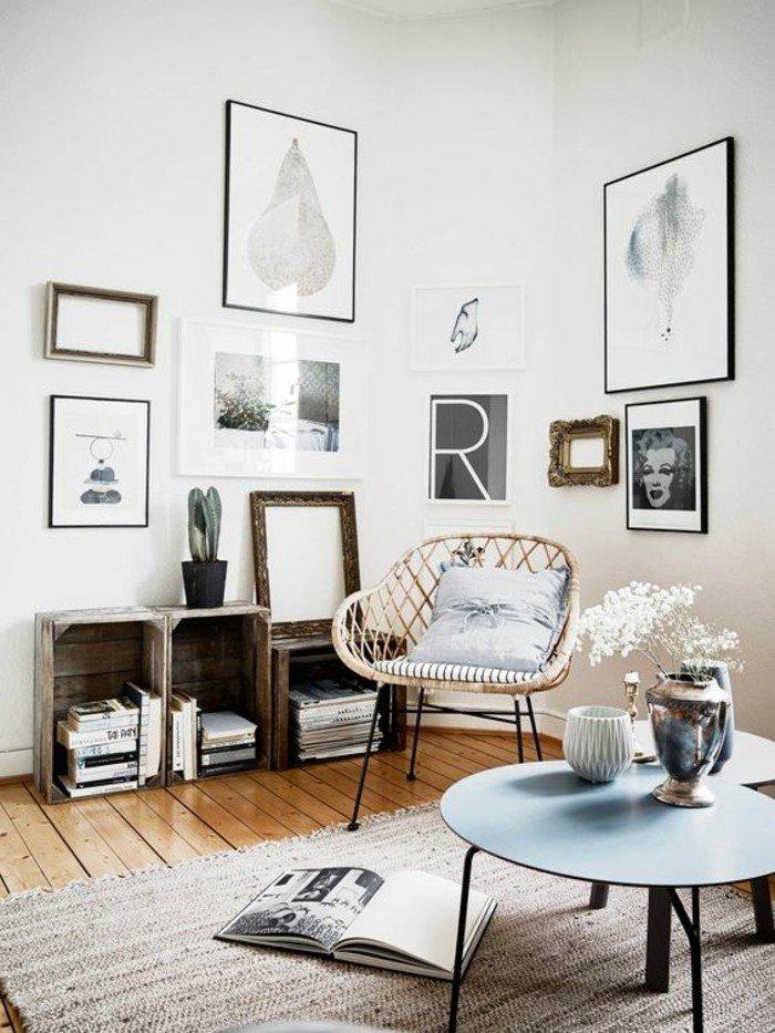 blauer runder Tisch, ein rustikaler Sessel mit blauem Kissen, viele Bilder, Wohnzimmer Ideen für kleine Räume