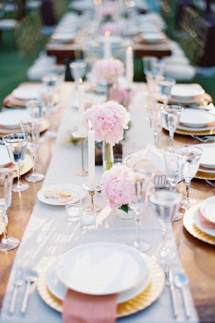 weiße Tischläufer, Vasen mit rosa Blumen, weiße Kerzen, Gläser für Wein, Blumen Tischdeko im Glas