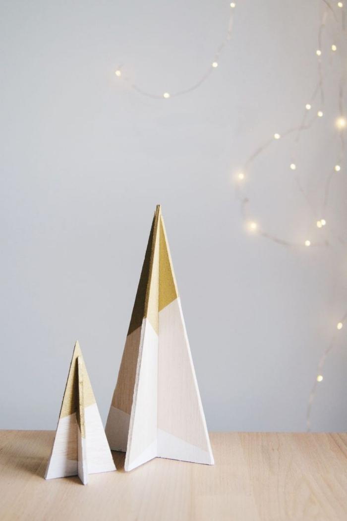 selbstgemachte tannenbäume aus holz dekoriert mit goldener und blauerfarbe, weihnachtsbaum basteln