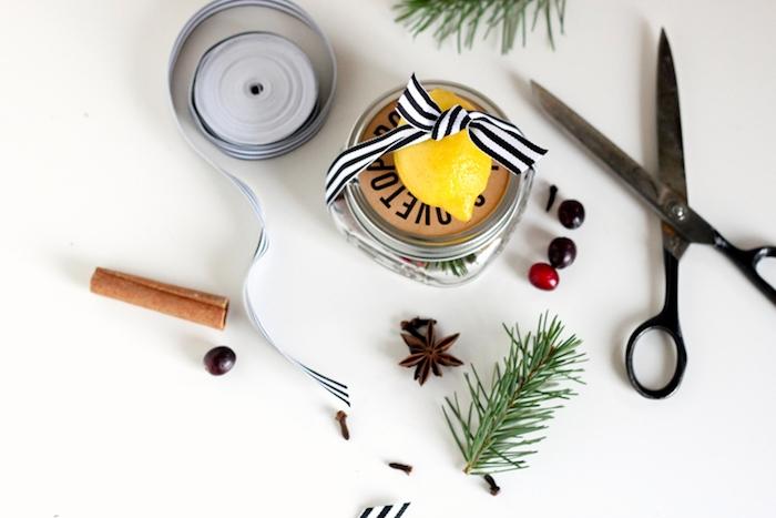 Kleines Einmachglas voll mit Tannenzweigen, Beeren und Zimt, Zitrone befestigt mit Dekoband am Deckel